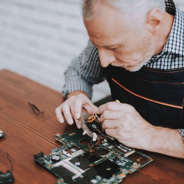 Trabajador sénior reparando una placa de ordenador.