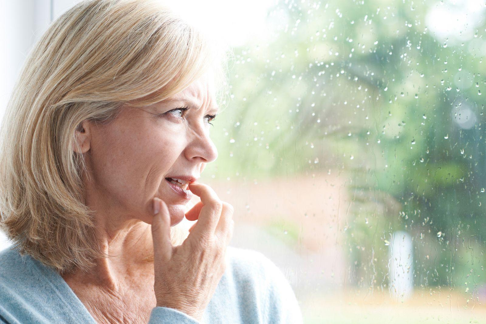 Mujer con ansiedad junto a ventana