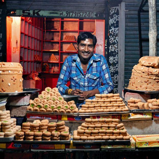 Un hombre vendiendo dulces típicos en la India (Bigstock)
