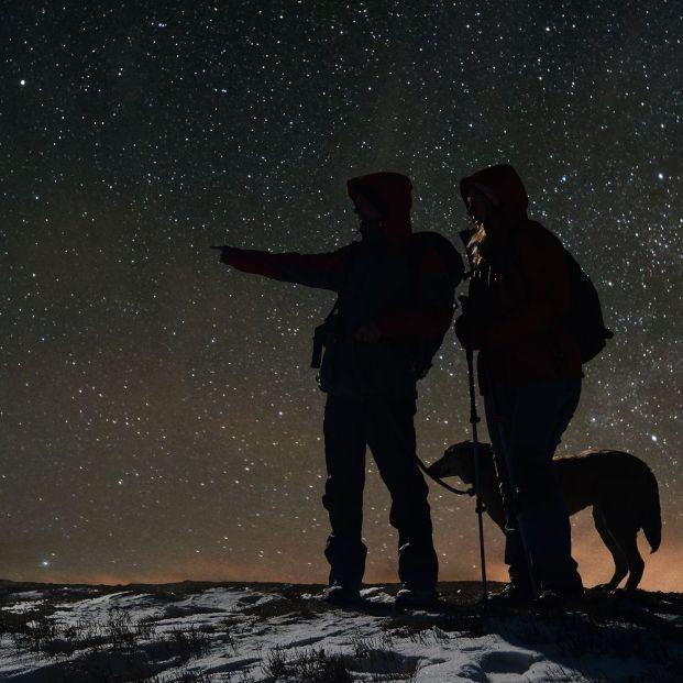 Personas acompañadas de un perro haciendo senderismo nocturno