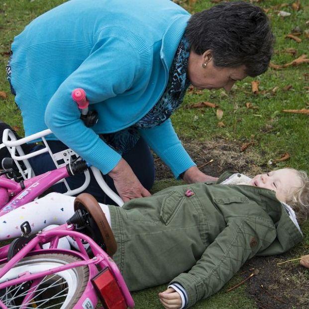 Primeros auxilios a una niña que se ha caído de una bicicleta (bigstock)