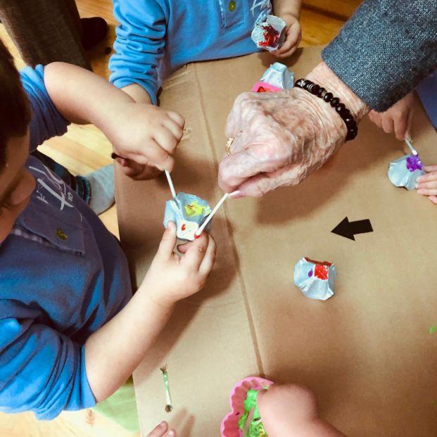 Niños y mayores haciendo manualidades en la guardería Hadas y Duendes.