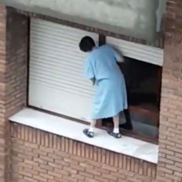 Acto temerario: una mujer sale al alféizar de su ventana para limpiar la persiana