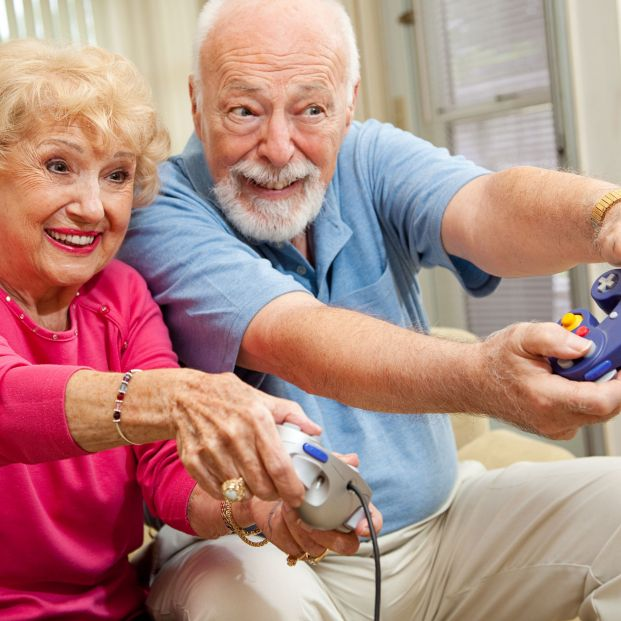Adultos jugando a videojuegos (bigstock)