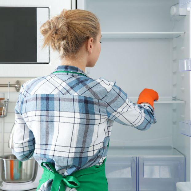 Mujer limpiando nevera para conservar los alimentos (bigstock)
