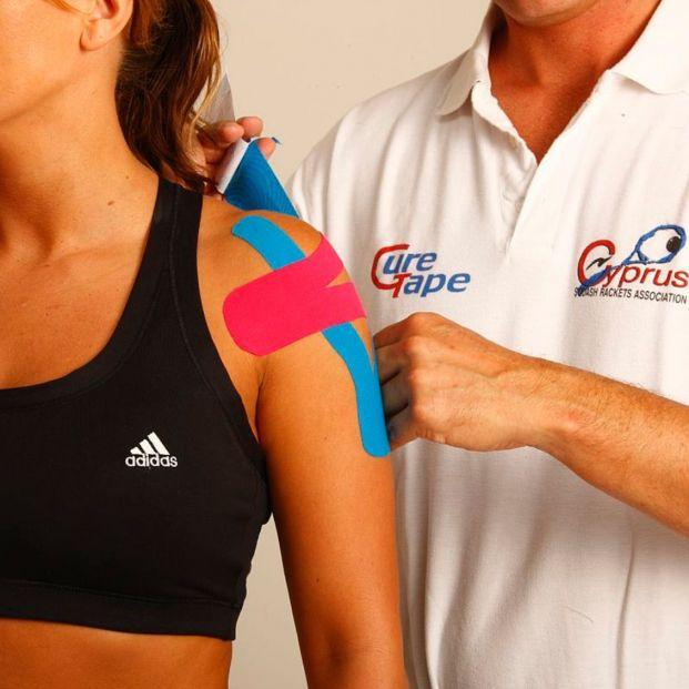 Fisioterapeuta colocando kinesiotaping con bandas de colores (Creative commons)
