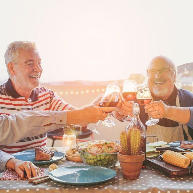 Personas mayores comiendo en grupo felices