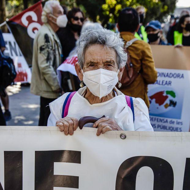 Mujer mayor sostiene pancarta manifestacion contra recorte presupuesto